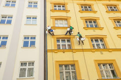 Low angle view of window washers hanging outside building Stock Photography