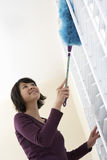 Low Angle View Of Woman Dusting. Low angle view of a smiling Asian woman dusting window royalty free stock photo