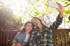 Low angle view of woman taking selfie with daughter while making faces against trees Stock Photos