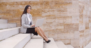 Low angle view of woman using laptop outdoors Stock Photo