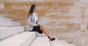 Low angle view of woman using laptop outdoors Stock Photos