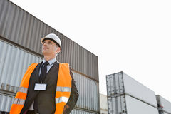 Low angle view of worker standing against cargo containers in shipping yard Royalty Free Stock Photo