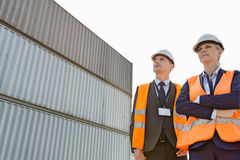 Low angle view of workers standing against cargo containers Royalty Free Stock Photography