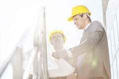 Low angle view of young businessman in hard hats reviewing blueprint on stairway Stock Photos