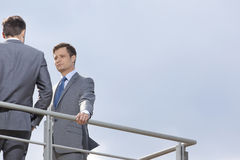 Low angle view of young businessman looking at coworker against clear sky Royalty Free Stock Photos