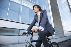 Low angle view of young businessman riding bicycle by building Stock Photo