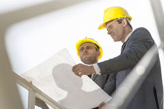 Low angle view of young businessmen holding blueprint against clear sky Stock Photography