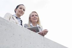 Low angle view of young businesswomen with digital tablet looking away while standing on terrace against sky Stock Image