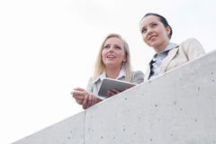 Low angle view of young businesswomen with digital tablet looking away while standing on terrace against sky Stock Photos