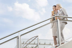 Low angle view of young businesswomen with disposable coffee cups looking away while standing by railing against sky Stock Photo