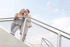 Low angle view of young businesswomen with disposable coffee cups standing by railing against sky Royalty Free Stock Images