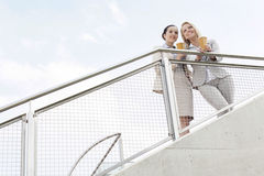 Low angle view of young businesswomen holding disposable coffee cups while standing by railing against sky Stock Photos