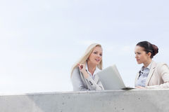 Low angle view of young businesswomen with laptop discussing while standing on terrace against sky Royalty Free Stock Images