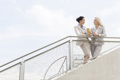 Low angle view of young businesswomen talking while standing by railing against sky Stock Image