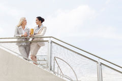 Low angle view of young businesswomen talking while standing by railing against sky Royalty Free Stock Photos