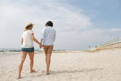 Caucasian couple walking at beach on a sunny day. Low angle view of young Caucasian couple walking at beach on a sunny day stock photos