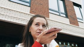 Woman send audio message with smartphone. Low angle view of young caucasian woman sending audio message on her mobile phone. Modern building at the background stock video
