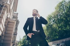 Low angle view of a young handsome bearded business man in a classy suit talking on his mobile outdoors at the sunny spring day. He looks stunning royalty free stock images
