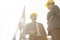 Low angle view of young male architect having discussion on stairway against clear sky Stock Images