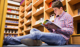 Low angle view of young man reading book  in library Stock Photos