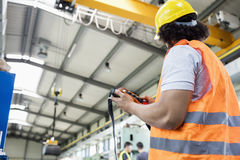 Low angle view of young manual worker operating crane in factory royalty free stock photography