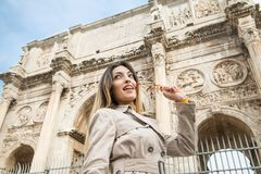 Tourist at Arch of Constantine monument in Rome. Low angle view of young pretty tourist woman smiling looking out eyeglasses in mouth, in background arch of Royalty Free Stock Image