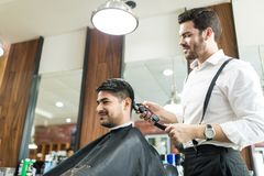 Professional Barber Trimming Client`s Hair In Salon stock photo