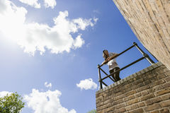 Low angle view of young woman leaning on railing Stock Images