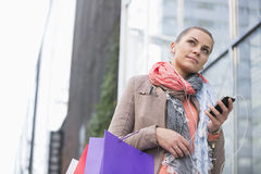 Low angle view of young woman listening to music while shopping Royalty Free Stock Images
