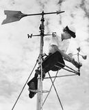 Low angle view of a young woman mending a weather vane. (All persons depicted are no longer living and no estate exists. Supplier grants that there will be no Stock Images