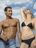 Low angle view of a young woman posing with a young man looking at her Stock Image