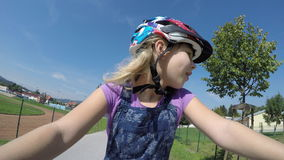 Low angle wide shot of young girl riding bike in city on a sunny day. stock video footage