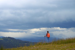 Wide shot of woman with hiking poles on mountain summit Royalty Free Stock Image