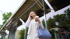 Low angle young business woman talking on cell phone during coffee break outside. Low angle of young business woman talking on cell phone during coffee break stock video footage