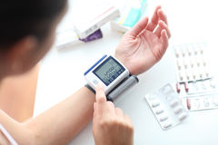 Low blood pressure. Young woman measuring her blood pressure stock images