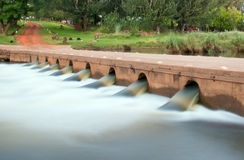 Low bridge with water. Flowing through pipes, slow shutterspeed to smudge movement Royalty Free Stock Photo