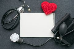 Low carb, low carb high fat LCHF, Keto, ketogenic diet mockup. With white notebook, red thread heart with tonometer on grey table. Benefits, What Do I Eat, How Royalty Free Stock Images