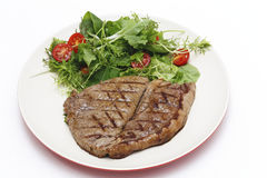 Low carb steak and salad. Low-carb meal of grilled rump steak with a home-grown salad mix and cherry tomatoes royalty free stock photography