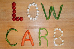 Low carb text. The text 'low carb' written with fresh vegetables on a wooden background royalty free stock image