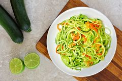 Low carb zucchini noodles on white marble. Low carb zucchini noodle dish with carrots and lime on white marble background, overhead view royalty free stock photography