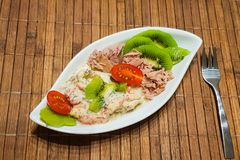 A low carbohydrate diet. Healthy low-carbohydrate food in small bowl, lunch with tomatoes, tuna, kiwi, shrimp homemade sugar-free sauce stock photography