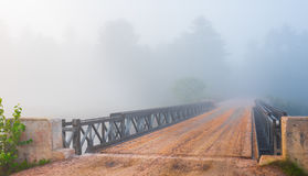 Low cloud in bright mist.  single lane road, steel & timber bridge into vanishing forest. Royalty Free Stock Photos