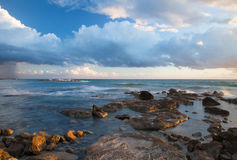 Low clouds above the stony shore of the sea. Seascape Stock Photography