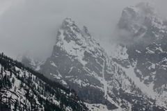 Low clouds in high altitude. The Grand Tetons peaking through a hole in the clouds Royalty Free Stock Photos