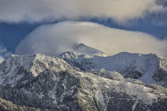 Low Clouds on Lone Peak. Snow covers Lone Peak that stands at 11253 feet above the Salt Lake City valley in Utah USA which is part of the Wasatch Mountains Royalty Free Stock Image