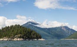 Low clouds surround mountains at lake Royalty Free Stock Image