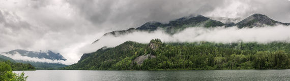 Low clouds surround mountains at lake Royalty Free Stock Images