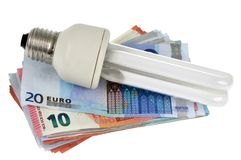 Low consumption light bulb placed on a wad of banknotes stock photo
