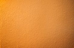 Wall surface with grainy orange texture. Low contrasted, soft texture of grainy wall surface suitable for background royalty free stock photo