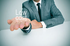 Low cost. A businessman sitting in a desk showing the text low cost in his hand Stock Images